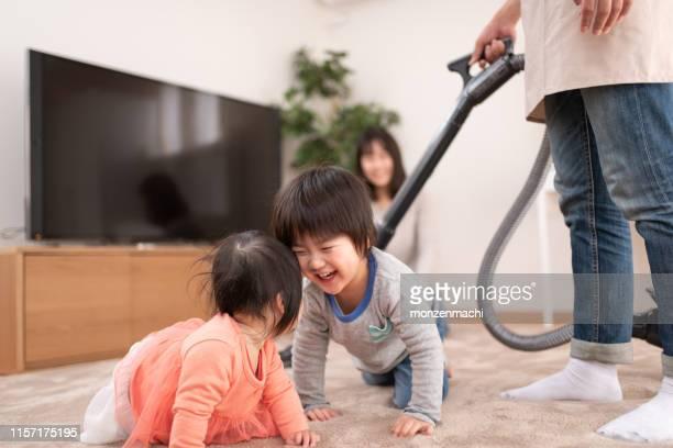 stay-at-home-vater staubsauger im zimmer mit kindern - stay at home father stock-fotos und bilder
