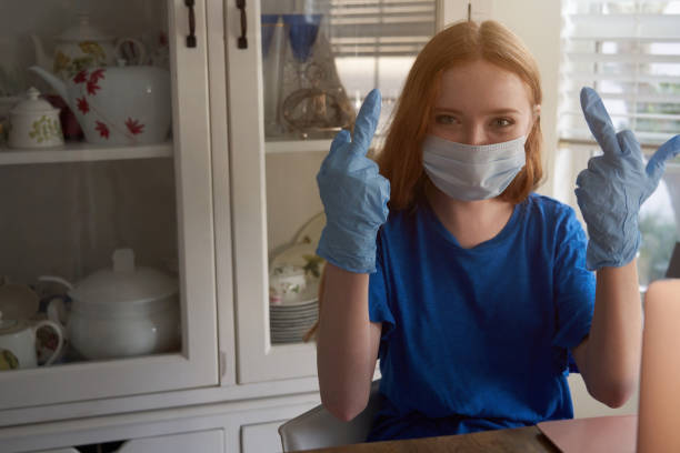 Staying at home young woman wearing surgical mask and rubber gloves during COVID-19 quarantine shows middle finger gesture