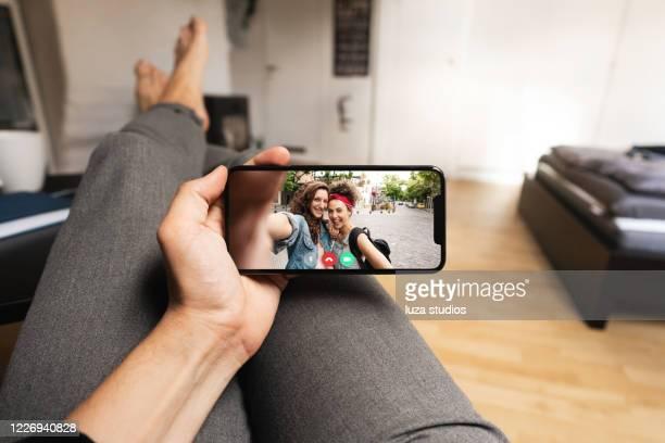 bleiben sie mit freunden auf videoanruf von zu hause verbunden - horizontal stock-fotos und bilder