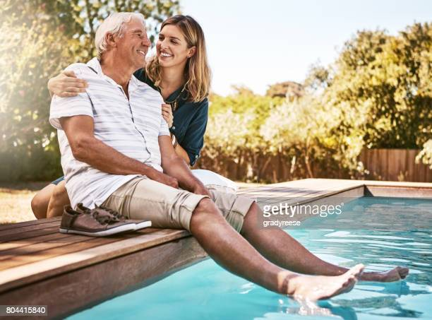 staying cool by the pool with pops - old man young woman stock photos and pictures