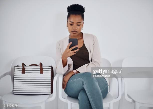 rimanere impegnati durante l'attesa in coda - borsetta nera foto e immagini stock