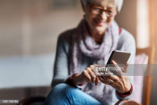 staying smart tech savvy in her senior years - mobile app stock pictures, royalty-free photos & images