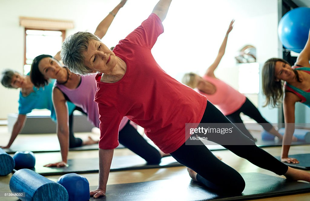 Staying supple in her senior years with pilates : Stock Photo