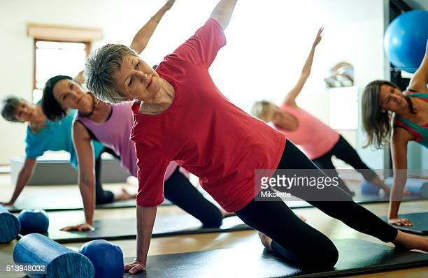 staying supple in her senior years with pilates - mat stock pictures, royalty-free photos & images