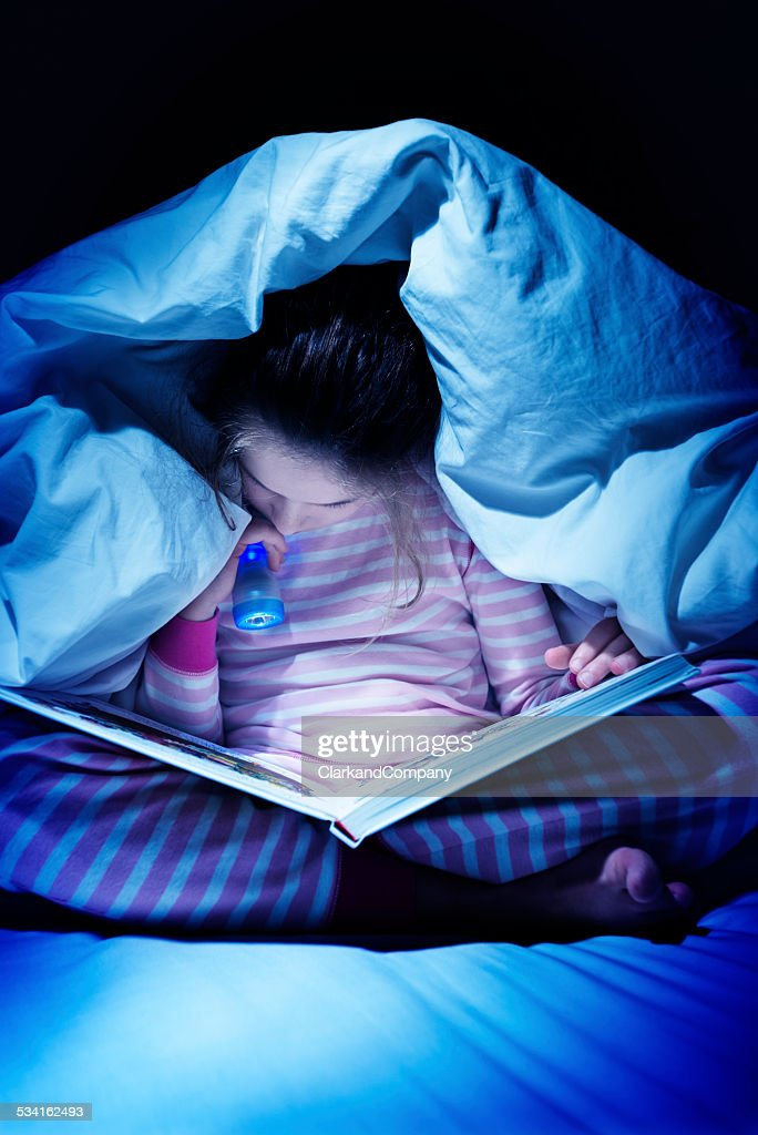 Staying Up Late Reading Under The Bed Covers : Stock Photo