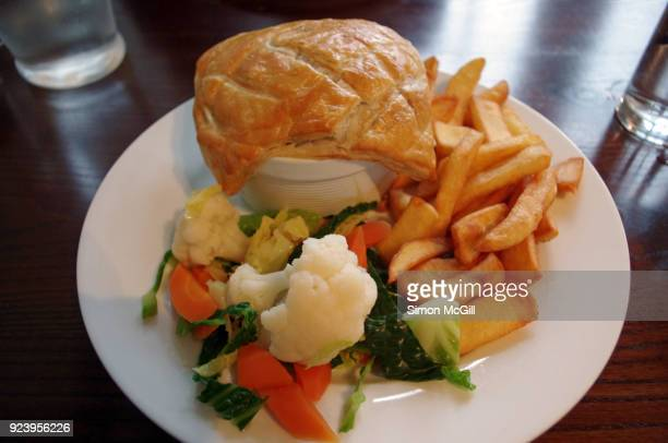 Steak and ale pie served with potato chips and steamed vegetables