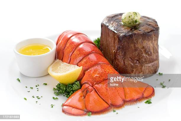 A steak and lobster with lemon