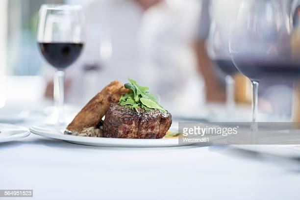 Steak and red wine on table in restaurant