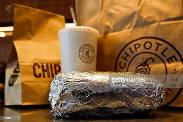 A steak burrito is arranged for a photograph with a drink and bags of chips at a Chipotle Mexican Grill Inc restaurant in Hollywood California US on...