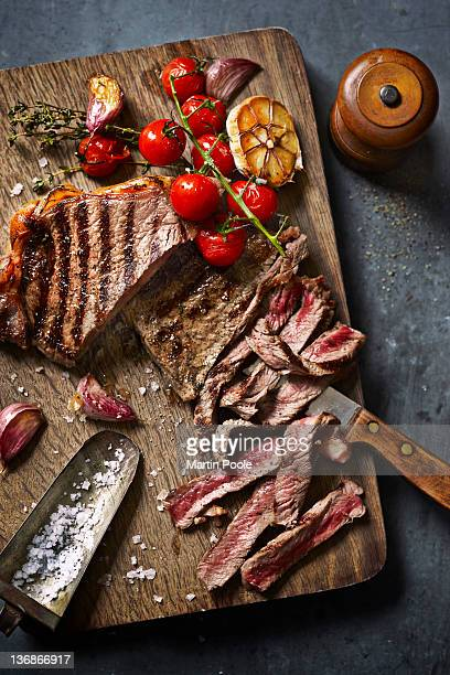 steak cut on board with roasted veg