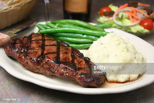 Steak dinner with mashed potatoes and steamed green beans