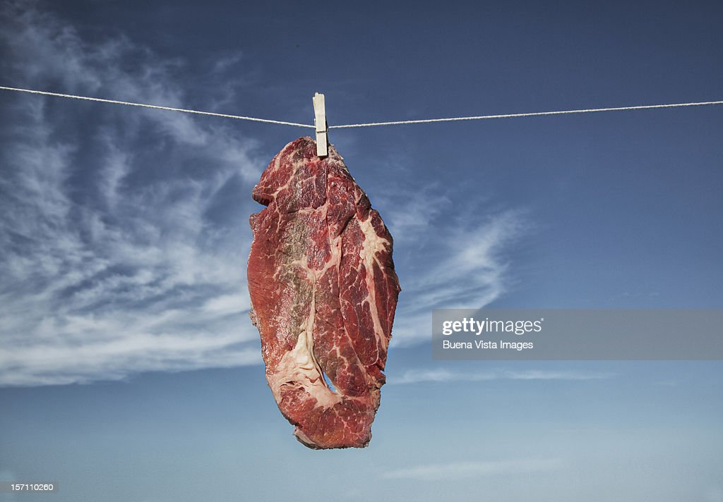 A steak hanging to dry on a washing-line : Stock Photo