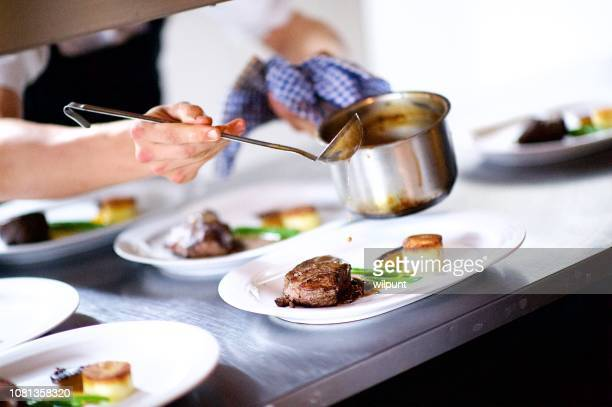 steak on a plate being prepared in a chef's kitchen sauce pouring - porzione di cibo foto e immagini stock