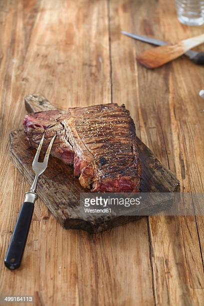 Steak on cjopping board on wooden table