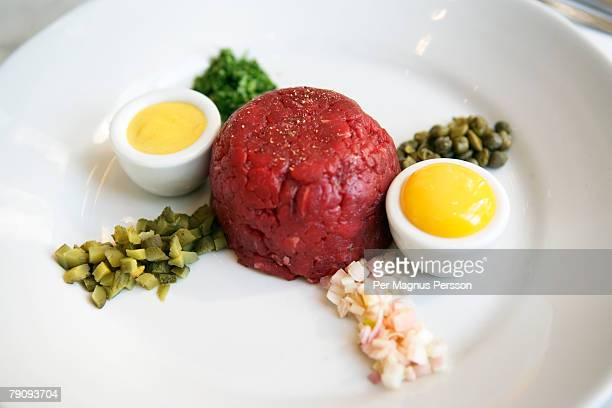 Steak tartare with eggs onions cucumber and capers.
