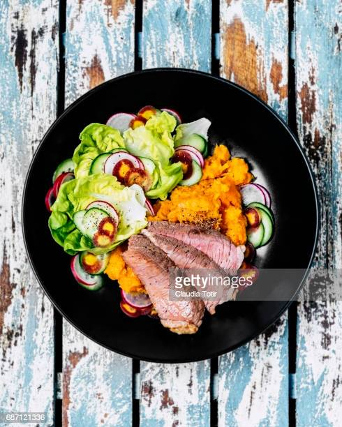 Steak with sweet potatoes and salad