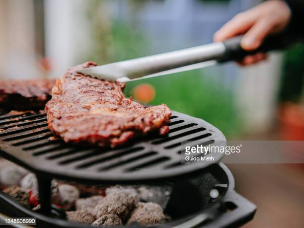 bbq steaks and sausage on a flame grill. - guido mieth stock pictures, royalty-free photos & images