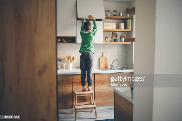 stealing cookies from the kitchen cabinet - pericolo foto e immagini stock