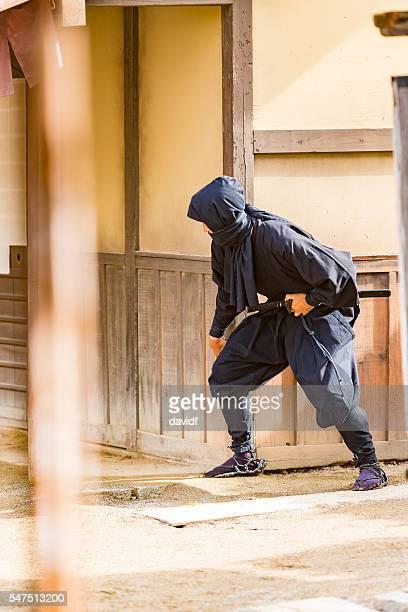 stealthy japanese ninja sneaking through a traditional village - ninja fotografías e imágenes de stock