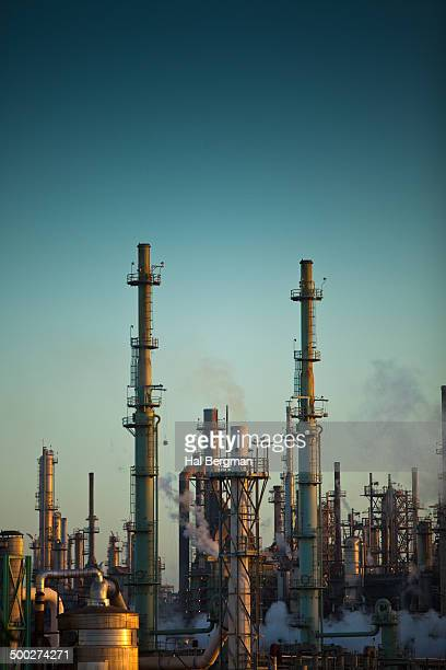 CONTENT] Steam and smoke rise up from among the fractional distillation towers and smoke stacks at a huge chemical plant and refinery complex near...