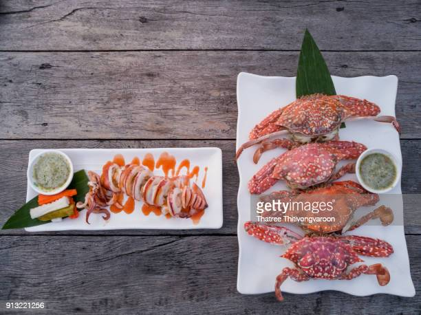 Steam crabs and grilled octopus on wooden table