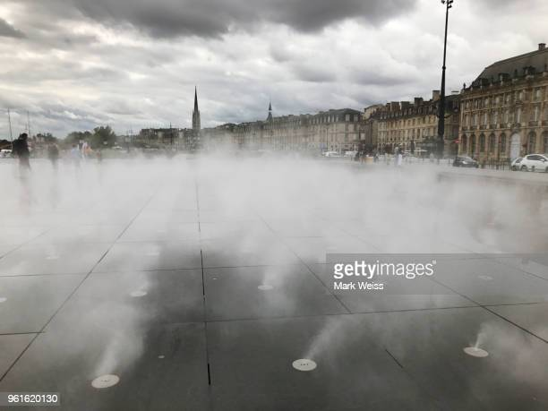 steam emitting from ground of the mirror, mirror d'eau with 18th century buildings and basilica saint michel in the background dramatic cloudy sky in bordeaux, france - mirror steam stock photos and pictures