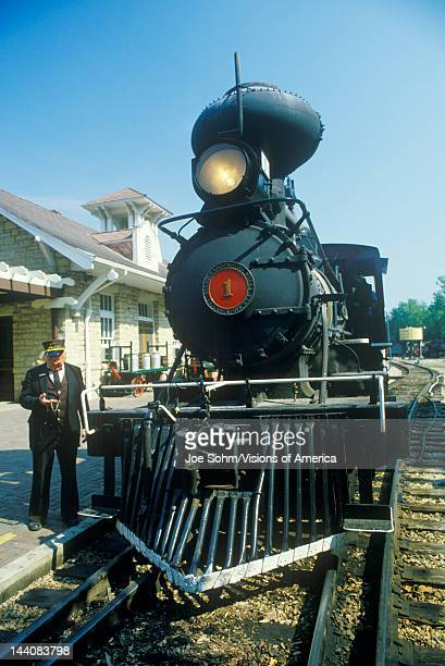 A steam engine conductor as he stands near the cowcatcher on the front Eureka Springs Arkansas