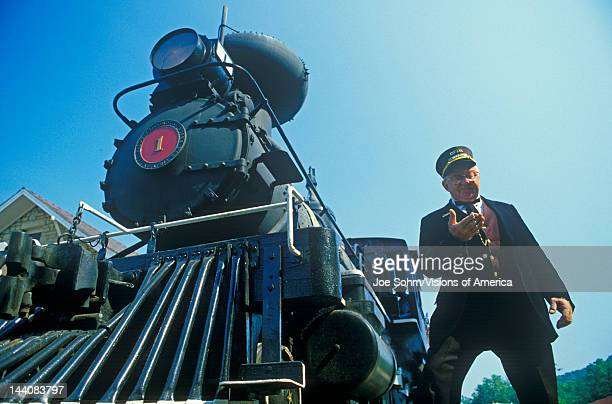 A steam engine conductor checks the time as he stands near the cowcatcher on the front Eureka Springs Arkansas