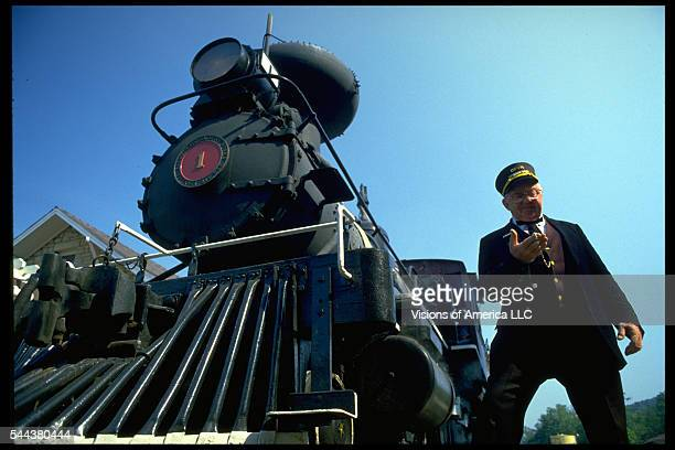 A steam engine conductor checks the time as he stands near the cowcatcher on the front Eureka Springs Arkansas 1986