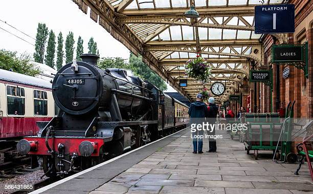 A steam engine enters Loughborough station as enthusiasts and passengers look on