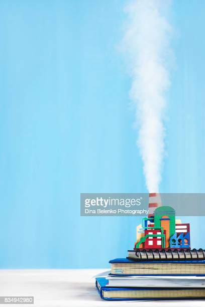 Steam engine papercraft. Still life with tiny industrial plant and rising smoke on a pastel blue background.
