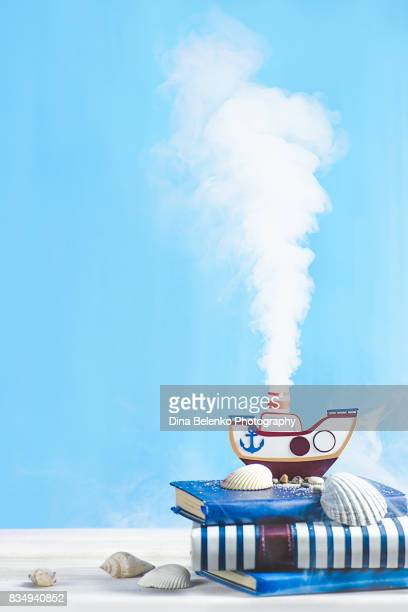 Steam engine papercraft. Still life with tiny steamboat on a pastel blue background.