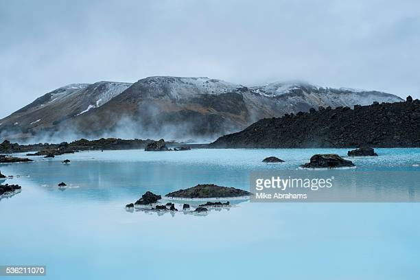 Steam hangs over the blue water from the thermal ponds created by the power station at Svartsengi The Blue Lagoon Iceland