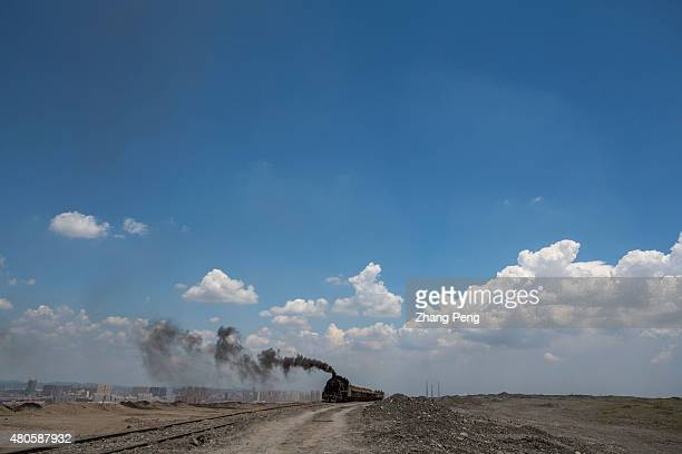 Steam locomotive emitting black smoke into the blue sky transporting waste coal cinders is driving on the highland which is heaped up by waste...