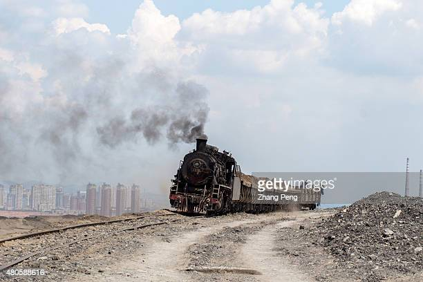Steam locomotive, emitting black smoke into the blue sky, transporting waste coal cinders, is driving on the highland which is heaped up by waste...