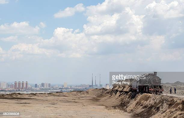 A steam locomotive is dumping waste coal residues transported from a power plant The waste coal residues have heaped up to form a highland in the...