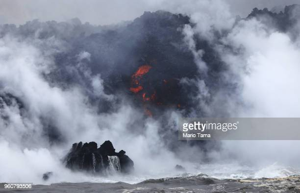A steam plume rises as lava enters the Pacific Ocean after flowing to the water from a Kilauea volcano fissure on Hawaii's Big Island on May 20 2018...