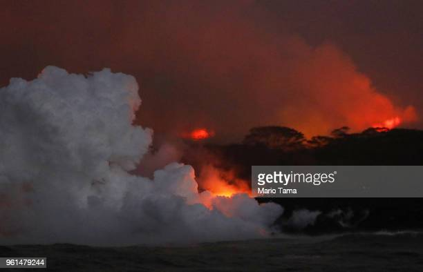 A steam plume rises as lava enters the Pacific Ocean at dawn after flowing to the water from a Kilauea volcano fissure on Hawaii's Big Island on May...