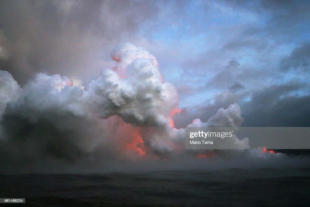 Steam plumes rise and lava glows as it enters the Pacific Ocean at dawn, after flowing to the water from a Kilauea volcano fissure, on Hawaii's Big Island on May 22, 2018 near Pahoa, Hawaii. Officials are concerned that 'laze', a dangerous product produced when hot lava hits cool ocean water, will affect residents. Laze, a word combination of lava and haze, contains hydrochloric acid steam along with volcanic glass particles.