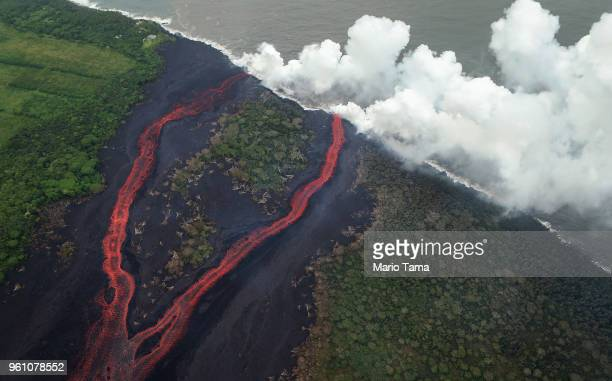 Steam plumes rise as lava enters the Pacific Ocean after flowing to the water from a Kilauea volcano fissure on Hawaii's Big Island on May 21 2018...