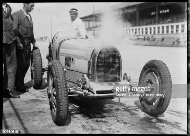 Steam pours out of Varzi�s Bugatti Type 51 racing car, with water cascading down its radiator. Varzi and mechanics look on in consternation. An...