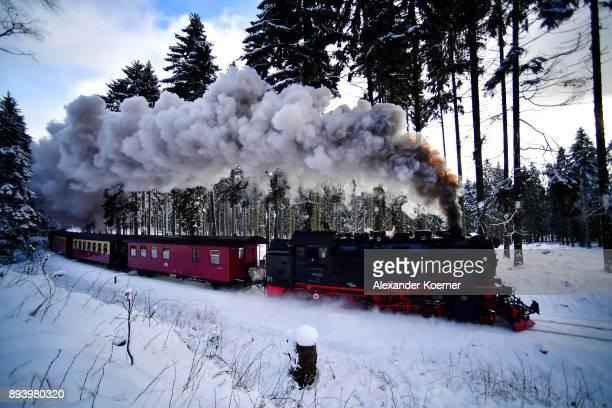 A steam powered locomotive of the Harz Narrow Gauge Railways travels through snow towards the station Brocken on December 16 2017 in Wernigerode...