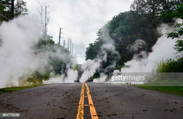 TOPSHOT Steam rises from a fissure on a road in Leilani Estates subdivision on Hawaii's Big Island on May 4 2018 Up to 10000 people have been asked...