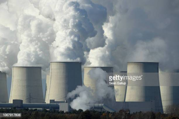 Steam rises from the cooling towers of the Jaenschwalde coalfired power plant on November 15 2018 near Peitz Germany The Jaenschwalde power plant is...