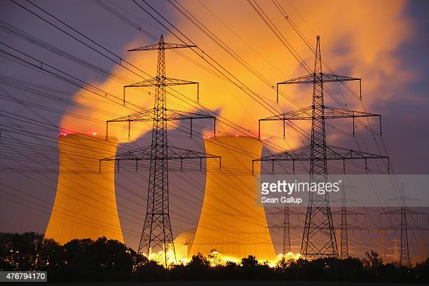 Steam rises from the Grafenrheinfeld nuclear power plant as electricity pylons stand before it at night on June 11 2015 near Grafenrheinfeld Germany...