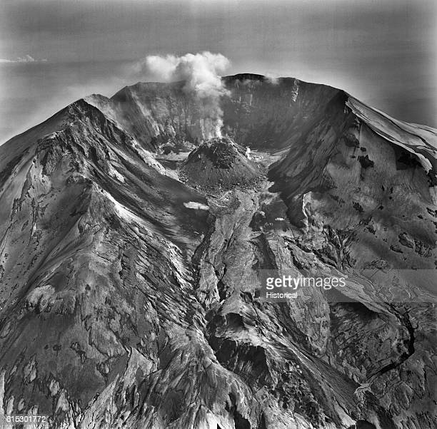 Steam rises from the growing lava dome of Mount Saint Helens. A narrow mud flow from a small eruption in late May descends from the dome. | Location:...
