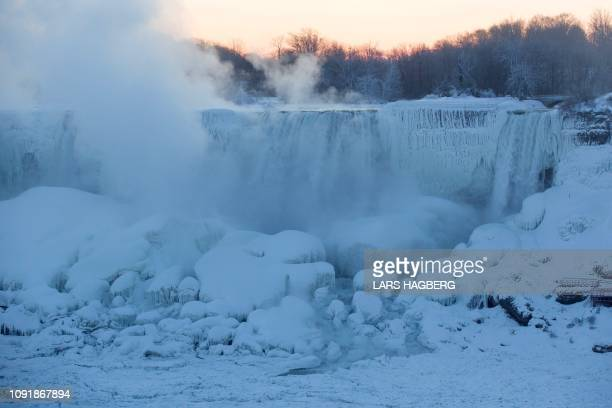 Steam rises from the US Niagara Falls before sunrise in Niagara Falls Ontario Canada on January 31 2019 A brutal cold wave moved eastward on January...