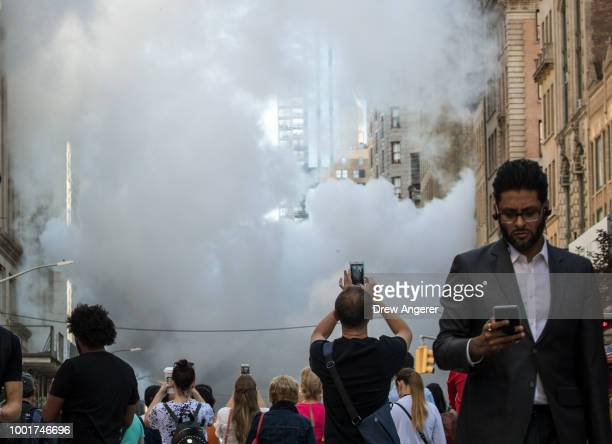 A man takes a photo with his smartphone near the site of a steam pipe explosion on Fifth Avenue near the Flatiron District on July 19 2018 in New...