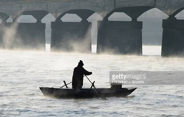 Steam rises off the freezing water as a Chinese man rows his boat along the Yalu River between China and North Korea some 70 kms north of the North...