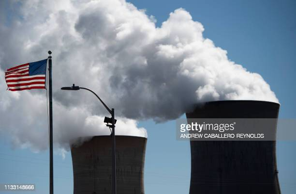 Steam rises out of the nuclear plant on Three Mile Island, with the operational plant run by Exelon Generation, in Middletown, Pennsylvania on March...